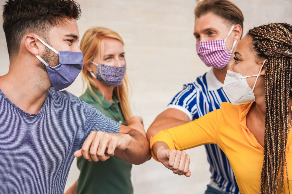 Young people friends bump their elbows instead of greeting with a hug - Avoid the spread of coronavirus, social distance and friendship concept - Wearing promotional item masks